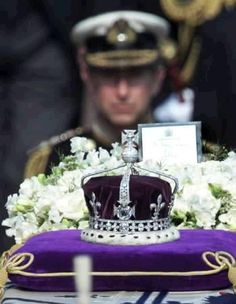 Prince Charles is seen behind the coronation crown as he follows the coffin of the Queen Mother during the procession to the lying-in-state at Westminster Hall in central London on this day, April 5, 2002. The coveted Koh-i-Noor diamond forms the centerpiece of the crown. Photo by Russell Boyce