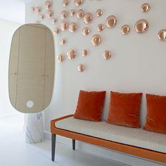 Une entrée très sobre et design avec une banquette moderne couleur mandarine avec miroir oval avec pied en marbre. Décoration murale rose.