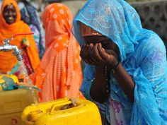 A woman drinks from a public fountain at a village in Assab Eritrea
