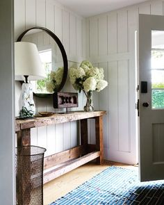 Gorgeous entryway with a round mirror above a console table.