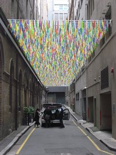 A colorful ceiling composed of thousands of long, multi-colored strands along Sydney's Bridge Lane.