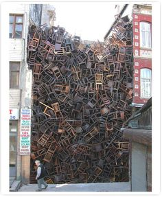 Chairs stacked between two buildings by Colombian sculptor Doris Salcedo.