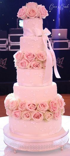 Large 5 tier wedding cake with fresh roses that's soft and romantic.