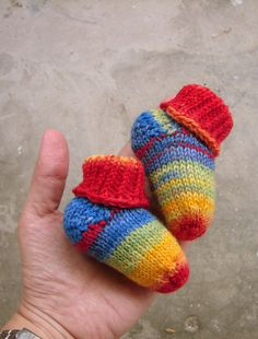 These rainbow striped newborn socks are really Stay-On. I used my own pattern to knit them by hand. Material is real thin wool sock yarn, in blue, green, yellow, red.