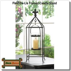 Fleur De Lis Framed Candle Stand - Oh la la! Candlelight with a touch of European flair is a surefire way to amp up the style in your room. This metal candle stand features a black rod framework topped with a fleur-de-lis finial. Inside, a clear glass candle cup hangs from a simple metal frame that will let the light shine bright.