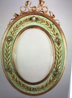 """A Fabergé  photograph frame. As described in Chapter Three: """"He picked up the enamelled oval guilloche photograph frame that stood next to the backgammon board he had earlier been playing on. The pale apple-green enamel was decorated with laurel leaves wrought in gold, interspersed with diamonds."""" Laurel Leaves, Cage, Photograph, Diamonds, Enamel, Apple, Board, Green, Decor"""