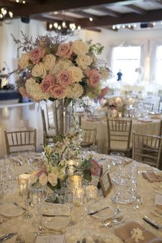 At the base of the centerpieces, collections of mercury glass votives and small florals including roses, freesias, dusty miller and variegated ivy filled the table . A fresh gardenia was placed on each napkin.