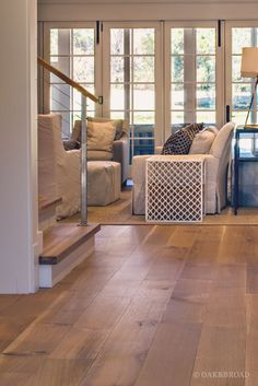 Wide Plank White Oak Hardwood Floor By Oak And Broad With Custom Stain | View Into Living Room With Matching Stair Treads | Discover more at http://OakAndBroad.com/nashville-tennessee-wide-plank-white-oak-flooring/