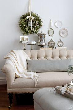 A white sofa, mercury glass, and hints of blue create a peaceful home interior.