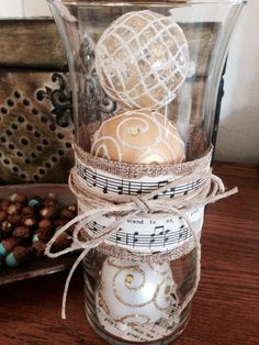 Thrifty Christmas decor: Vase and ornaments from the dollar tree. Christmas sheet music antiqued and glued to burlap ribbon. Cord tied around the middle.