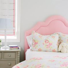 Pink and gray girl's bedroom features a pink candy stripe headboard on bed dressed in yellow and pink floral bedding next to a gray nightstand and white lamp under a white and pink roman shade.