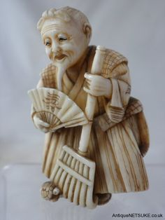 Ivory netsuke with the figure Jo standing with his broom a minogame at his feet. Late 19th C
