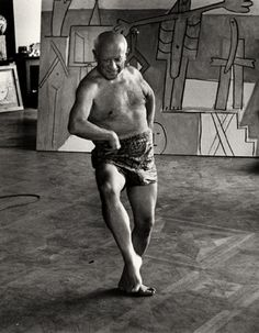 Pablo Picasso, wearing only shorts, dances in his studio.