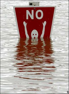 A sign disappearing under flood water