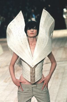 Top with huge wings made of balsa wood pierced with a lace-like pattern is worn over trouser