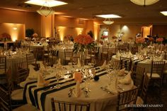 An inside wedding reception with navy & white striped table runners on round tables, with gold Chiavari chairs.