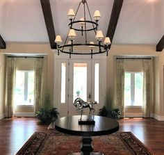 Now that is one way to make an entrance! Our client chose to outfit the windows on either side of her grand front door with tailored pleated drapes in a subtle textured pattern with matte black hardware to pull from her tiered chandelier. Drapery Styles, Matte Black, Entrance, Chandelier, Hardware, Windows, Ceiling Lights, Outfit, Pattern