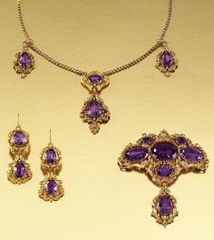GOLD, AMETHYST AND PASTE PARURE, 1840S Comprising: a pendant necklace, a pair of pendant earrings and a brooch/pendant of foliate and scroll répoussé work with bead detail, set with oval and pear-shaped amethysts, later snake chain link, 1860s, length approximately 390mm, three stones in necklace and one stone in brooch are paste, all drops on brooch, earrings and necklace detachable, later fitted case.