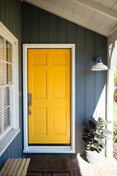 Front porch. Yellow door. Yellow front door. White lamp shade. Front porch light. Indoor outdoor lighting. Carson light. Rejuvenation Carson light. Wall sconce. Sconce for porch.