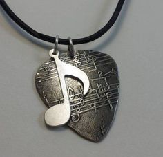 Fresh from the Bench collection addition . This guitar pick made from 18 gauge sterling silver ( 1mm thick) measures 1.2 by 1.1 inches . The music note charm measures about 3/4 inch long and is also 18 gauge sterling silver . Comes with a stainless steel ball chain or if you prefer a genuine black leather cord with slip knots that are adjustable.