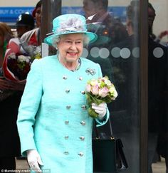 Joyful occasion: The Queen smiled happily as she accepted bouquets while dressed in a brilliant turquoise and silver coat