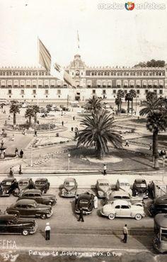 Vista del Zócalo y el Palacio Nacional en el centro histórico de la Ciudad de México.  La plaza aún tenía área verdes y jardines,  que se llenaban de gente y parroquianos durante el paseo dominical,  costumbre muy arraigada en ésa época.  Foto tomada probablemente en los años 20's.