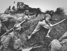 Japanese soldiers, supported by tankettes, assault Chinese positions. Nanchang, China. 1939.