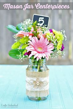 Need a quick & simple centerpiece idea? These gorgeous mason jar centerpieces with chalkboard stakes double as table numbers for a pretty & elegant wedding.