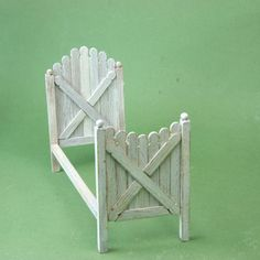 This junior sized bed for a dolls house is made from wooden stir sticks and built in the shape of traditional picket fence gates.