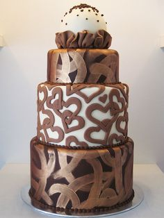 Chocolate, bronze dark and white chocolate wedding cake, accented with bronze brushstrokes, heart motif and topped with a giant white chocolate truffle by Artisan Cakes #weddingcakes #brownwedding