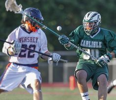 Carlisle's Thomas Nunez allows the ball as he is defended by David Stickler during the first period of the Mid-Penn boys lacrosse championship game at Landis Field.