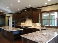 Colonial White Granite with Bordeaux Finish Cherry Cabinets and Mixed Brown Mosaic Backsplash   I particularly like the granite color!