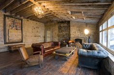 What a great space. Look at the texture...the walls, leather, rough hewn wood floors, exposed wooden beam ceiling...