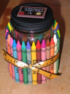 "Another pretty teacher gift is a ""Crayon Goodie Jar"". This was such a fun craft to make. You hot glue crayons around a half pint size canning jar. Tie on a ribbon and spray paint the lid black to represent a chalkboard. Glue on a school themed decoration for the top and fill with something sweet. (M's, Skittles, Hershey's Kisses, granola, jelly beans or whatever you like)."