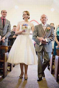 Noiva entrando com pai na igreja, com vestido curto de saia volumosa.