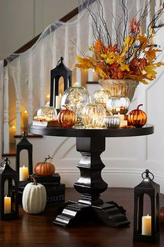 Want a simple yet impactful centerpiece that can take you from Halloween to Thanksgiving? Group faux pumpkins together made of glass and add flameless tea lights. It's a beautiful base to layer other key pieces into as the season progresses.