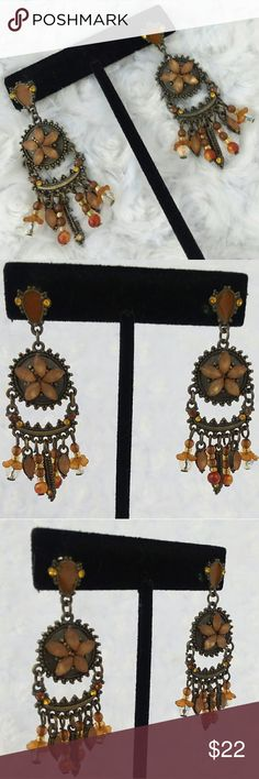 "VINTAGE Bronze Tones Chandelier Pierced Earrings These beautiful multimedia earrings have post backs with a brown enameled upside down teardrop with amber rhinestones on either side anchoring a bronze tone medallion with 5 tan moonglow lucite stones set in a flower. Hanging in chandelier style are multiple types of beads. Circa 1970s, they measure 2 1/4"" long by 3/4"" wide and are in like new condition. Vintage Jewelry Earrings"