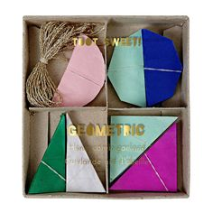 A stylish mini-garland with beautiful 3D geometric pennants crafted using honeycomb paper. The pennants are suspended from shimmering gold striped
