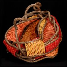 Tina Puckett | 'Dragon Pouch' The frame is made with bittersweet vine. The pouch is woven of reeds in colors reds, oranges, yellows and wine.