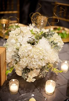 Brides: White Floral Gold Accented Centerpieces. Tables were decorated with white floral centerpieces accented with gold. The couple pasted gold and silver numerals to antique copies of their favorite books purchased from eBay to serve as table cards.