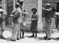 British policemen checking papers of Jewish people on a street in Jerusalem, British Mandate of Palestine; 1947.