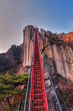 """Ponte suspensa na montanha Daedunsan, Coreia do Sul Ela tem só 10% da altura do Monte Everest, mas nem assim deixa o alpinismo parecer fácil. Como os rochedos despontam irregulares na montanha Daedunsan, só escalando a ponte vermelha para chegar ao topo de seus 878 m. Para a última fase da """"escalada"""", 127 degraus dão uma forcinha aos turistas."""