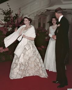 1954, Australia: Seen here leaving a state banquet during a tour of the Commonwealth which encompassed 44,000 miles, the Queen is wearing a one-shoulder gown created by Norman Hartnell, the royal couturier famously responsible for her Coronation and wedding outfits. (Gold lamé overlaid with lace and embroidered with gold thread)