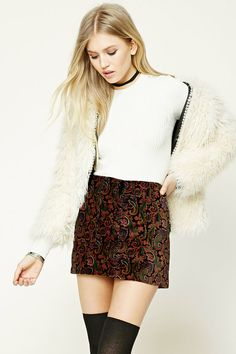 A velvet mini skirt featuring contrast stitching, front buttoned slant pockets, and a zip fly.