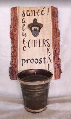 """Wandbord flesopener met opvangbakje voor de doppen. De tekst """"Proost"""" is in verschillende talen in het hout gebrand. Het bord is afgelakt, zodat het tegen weersinvloeden beschermd is. Het opvangbakje is afneembaar, zodat deze eenvoudig leeg te maken is. Het bord kan naar wens worden gemaakt, b.v. voorzien van initialen, (bedrijfs)naam of logo. Bottle Opener, Barware, Deco, Seeds, Decor, Deko, Decorating, Decoration, Tumbler"""