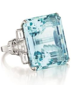 An Art Deco Aquamarine and Diamond Ring. Set with a rectangular cut-cornered aquamarine gauged to weigh approximately 30.00 to 35.00 carats, to the baguette and circular-cut diamond shoulders, mounted in platinum.