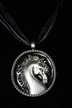 Horse head medallion on a black ribbon necklace. Hypoallergenic. Necklace measures an adjustable 17 - 19 inches in length. - $20.00