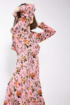 A wardrobe must-have for the 'pretty girl', this midi dress comes in a bold pink floral pattern, featuring long sleeves, an asymmetric hem and ruffle trim details. With tie at the waist.