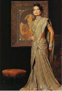 Regal and resplendent, this elegant purple and gold brocade ensemble is really a lehnga with the heavy dupatta draped so as to resemble a sari. The picture of Mumtaz Mahal, mounted in a heavy gilt, adds just the right touch of grandeur to the proceedings.
