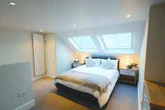 loft conversions bedroom in sw18 with velux windows, with a split level dressing room and showeroom